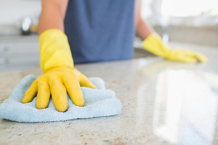 Woman cleaning the counter  in the kitchen