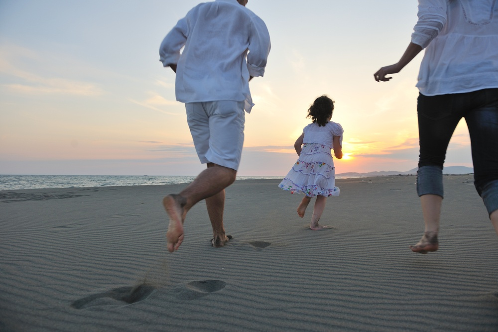 happy young family have fun on beach run and jump  at sunset.jpeg